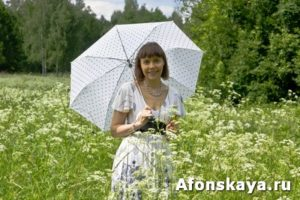 Young woman with white umbrella on a meadow