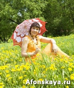 Woman with umbrella on meadow with dandelions