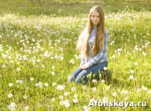 Young girl on meadow with white dandelions